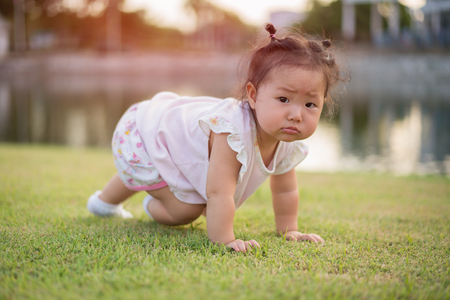 Asian little girl on lawn in the park.