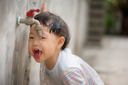 Baby asian girl drinking water from tap.