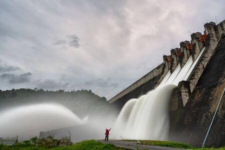 Traveler with a large dam gate. Dam with floodgate, Spillway on the Khun Dan Prakan Chon Dam in thailand.