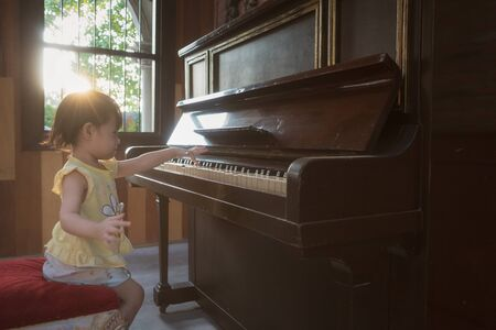 Asian little girls are playing the old piano.