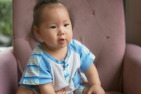 Asian baby girl drooling. 8 months old baby girl sit on sofa with drooling.