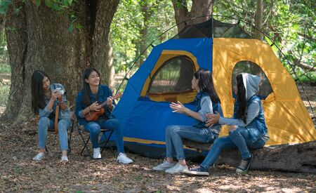 Group of teenage asian girls camping and resting at forest playing ukulele and take a photo happy together. Camping concept