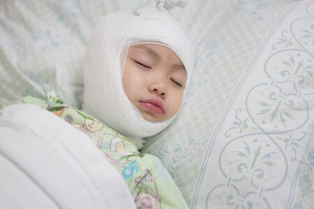 Little asian girl lying sick with bandaged head on bed at hospital. Baby girl injury and headache. Close-up shot