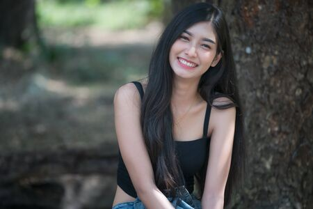Portrait of beautiful asian teenage girl look at camera and smiling in garden.