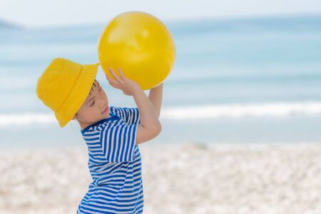 Little asian girl playing yellow ball on the beach in summer. Little girl have enjoy and happy, Happy family concept. Stock Photo