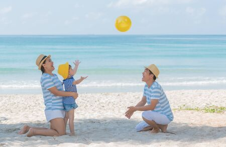 Little asian girl playing yellow ball with mom and dad on the beach in summer. Little girl have enjoy and happy with family in holiday, Happy family concept. Stock Photo