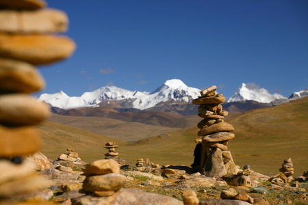 Tibetan plateau with snow covered Himalaya range and stone cairn in the front.