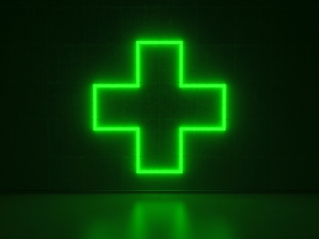 A green Neon Sign in Form of a Plus on a Wall of Concrete photo