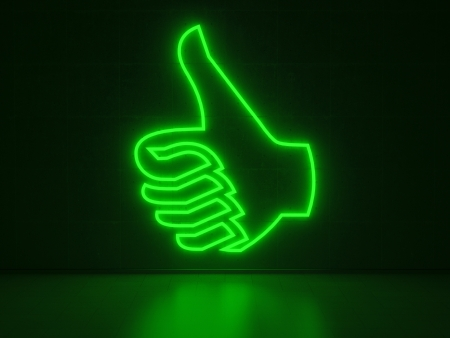 A green Neon Sign in Form of a Hand with Thumb Up on a Wall of Concrete photo