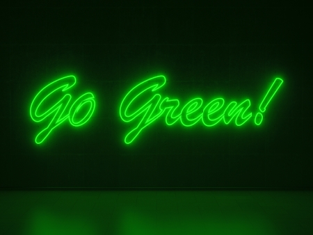 A green Neon Sign in Form of the Words Go Green on a Wall of Concrete photo