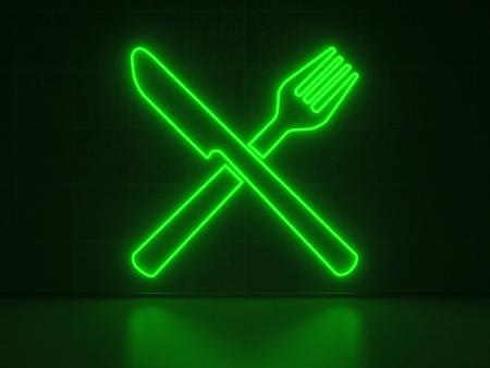A green Neon Sign in Form of Knife and Fork on a Wall of Concrete photo