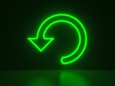 A green Neon Sign in Form of a Circled Arrow on a Wall of Concrete photo