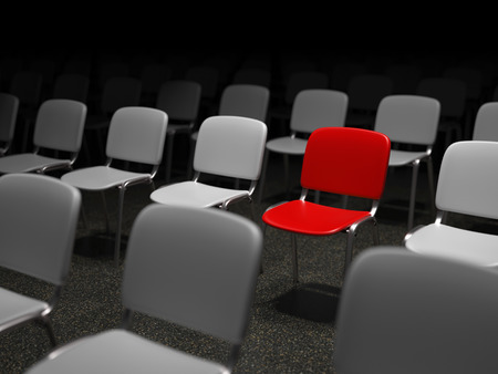 Group of chairs with a red chair standing out symbol for uniqueness photo