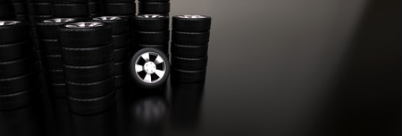 Several stacks of car tires on reflective floor photo