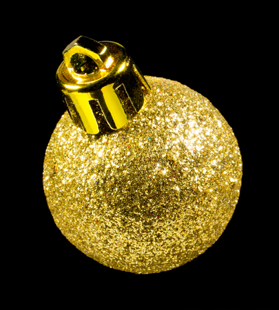 Single golden glitter Christmas bulb isolated on black background