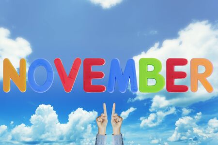 Hands point to wording NOVEMBER