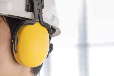 Man met veiligheidshelm en gehoorbescherming