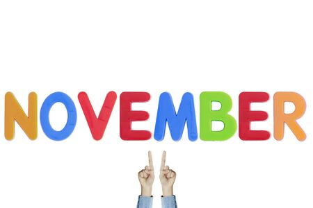 Hands point to wording NOVEMBER on white background Фото со стока