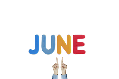 Hands point to wording JUNE on white background