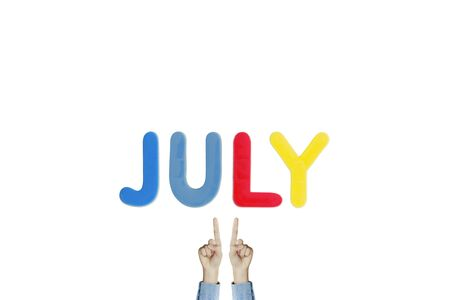Hands point to wording JULY on white background