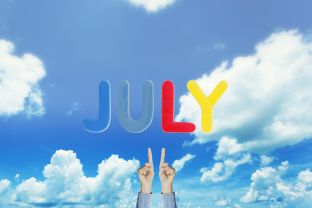 Hands point to wording JULY
