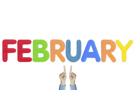Hands point to wording FEBRUARY on white background