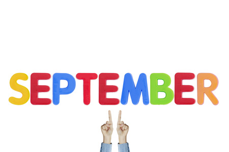 Hands point to wording SEPTEMBER on white background