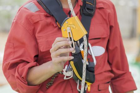 Inspector man showing rope access equipment Фото со стока