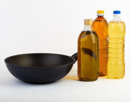 Pan with bottles of oil isolated on white Stock Photo