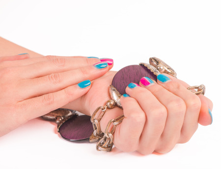 nailart: Woman hands holding accessories with new manicure isolated on white background