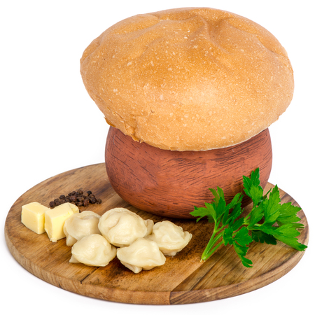 forced: meat pockets on the wooden plate served with piece of butter in the ceramic pot covered by fresh pastry