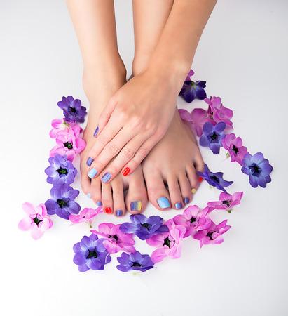 잘 다듬어 진 손과 pedicured 피트와 꽃 arond 흰색