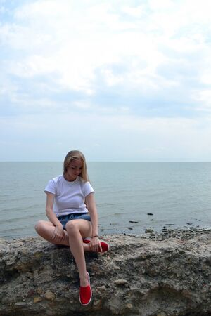 Young woman in white t-shirt relaxing by the sea Stok Fotoğraf