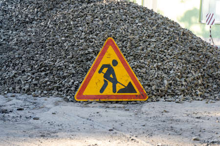 The sign of road works on red white barrier in front of a pile of gravel on a city street. Construction and repair of asphalt roads in a town