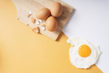 Top view - Eggshell fresh egg on wooden plate and fried egg. Foto de archivo