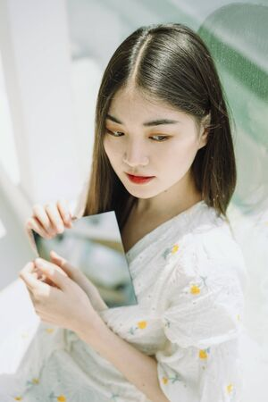 Beautiful asian young thai woman holding mirror plate with two hands.