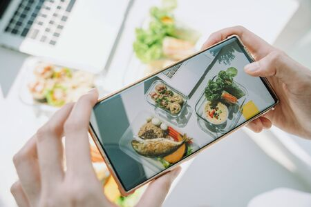 Top view of woman hand taking photo of healthy food on working office desk with smartphone. Copy space.