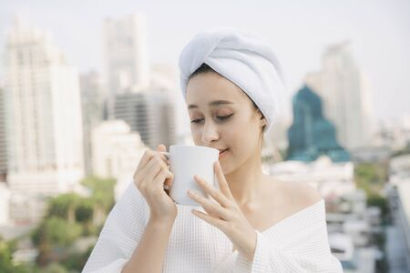 Young woman in white bathrobe enjoy hot coffee at apartment balcony over city background.