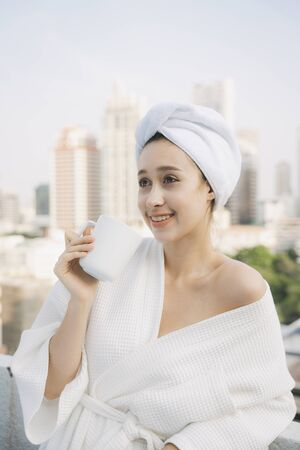 Young woman in white bathrobe enjoy hot coffee at apartment balcony over city background. Archivio Fotografico