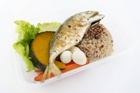 Deep fried mackerel with rice and boiled vegetables in a box. Isolate in white.