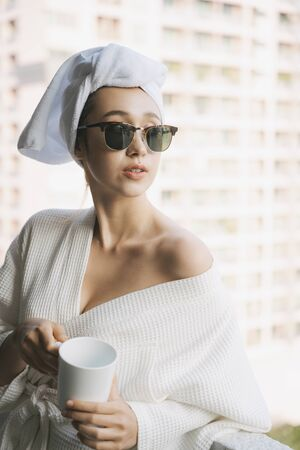 Young woman in white bathrobe wearing sunglasses holding cup of coffee at balcony in apartment room.