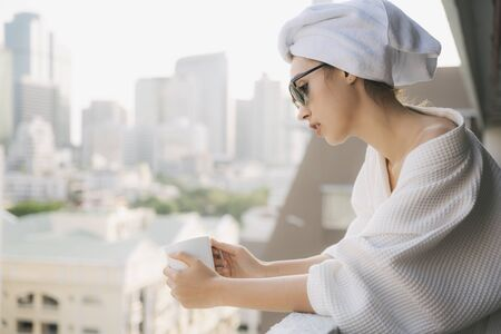 Copy space. Side view - Young woman in white bathrobe holding cup of coffee at apartment balcony.