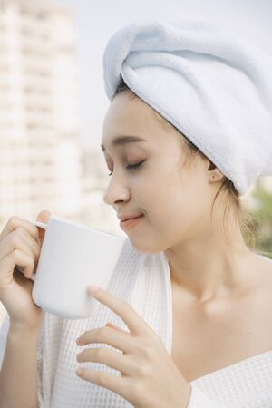 Side view close up - Young woman in white bathrobe enjoy hot coffee at apartment balcony over city background.