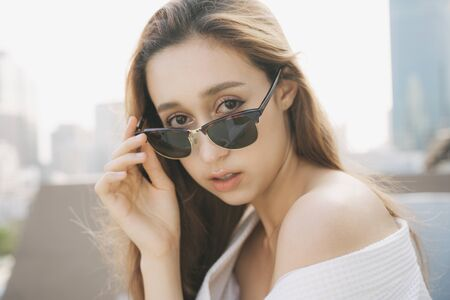 Close up of sexy young woman in white bathrobe wearing sunglasses isolated over city background. Apartment balcony.