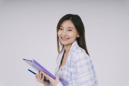Cheerful Thoughtful beautiful thai businesswoman holding clipboard isolated over white background.