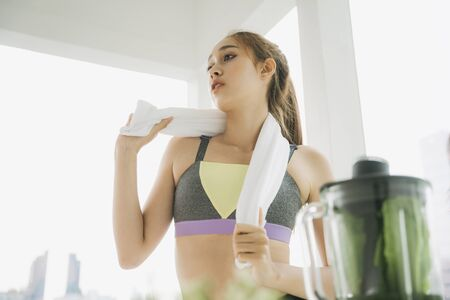 Beautiful healthy woman in sport bra and towel making healthy vegetable juice with mixing blending machine in the kitchen after exercising at home.