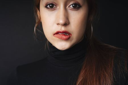 Close up portrait of pretty beautiful young woman wearing black sweater isolate over dark background. Woman using red lipstick. Cosmetic concept. Bitting lips posing.