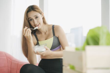 Beautiful woman in sportwear with natural make up isolated over white background. Healthy woman in sportbra enjoy eating yogurt with spoon from glass bowl on a couch. Quarantine at home.