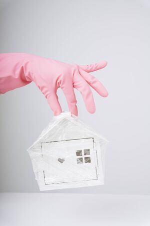 Hand of doctor wearing pink gloves holding a toy white house cover in plastic wrap. Doctor saving people in the house from Covid-19. Coronavirus concept.