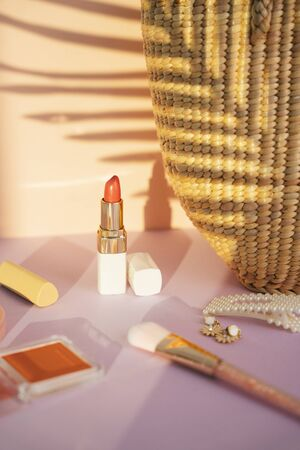 Close up of orange red lipstick made of nature material with woman accessories.